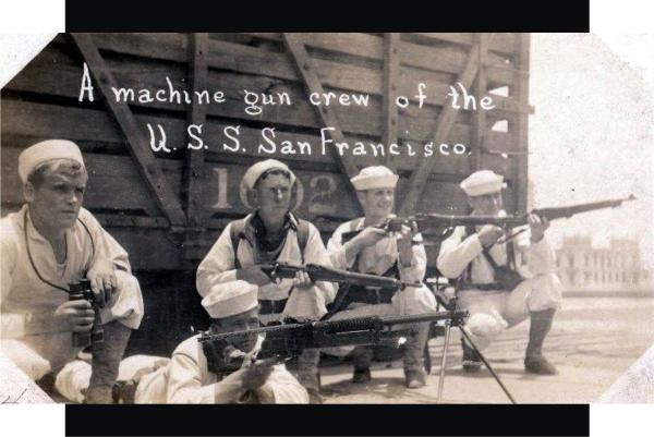 Un equipo de ametralladora del USS San Francisco en postura de ataque en el muelle, al fondo se ve el lado oeste del Edificios de Faros.